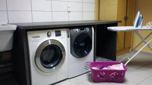 Buanderie pour les appartements avec lave linge et sèche linge.