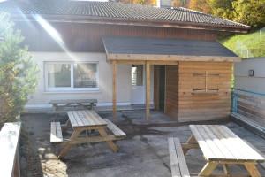 Terrasse aménagée avec tables et barbecue à gaz.
